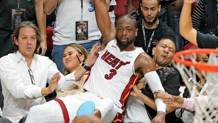 Legend and Teigen couldn't help but laugh as they shared photos of Dwayne Wade crashing on their seats while grabbing the ball on their Twitter accounts.